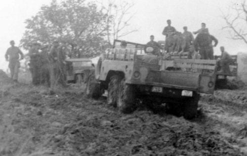 Trucks in the rain and mud on the newly constructed road leading to Ipo Dam, in the 103rd Infantry zone, 5/18/45. [Photo: U.S. Army Signal Corps, SC 312642] The photo caption states that the men, with the help ofrr a bulldozer, drag vehicles out of a muddy hole, but the helping is not evident.