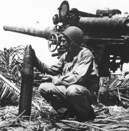 Maj. Wilber E. Bradt with a 5-inch naval gun his artillery put out of action on Baanga Is., the Solomon Islands, on August 17, 1943. This was one of two guns captured by the Japanese from the British in Singapore and emplaced on Baanga Island to defend the approaches to Munda airfield. [Photo; U. S. Army Signal Corps, 161-43-9009]
